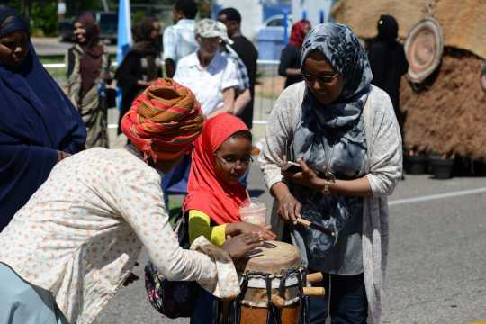 Photograph of a child playing a traditional Somali drum with help from adults