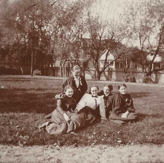 Black and white photograph of Students of St. Joseph's Academy relaxing on school grounds, 1897.