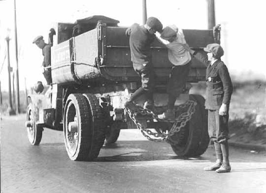 School Police gives warning to boys trying to hitch a ride on a truck.