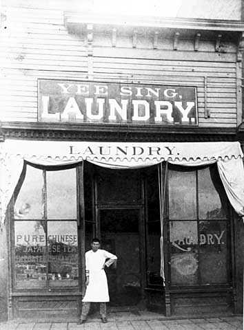 Yee Sing Woo standing in front of Yee Sing Laundry, 1319 Nicollet, Minneapolis