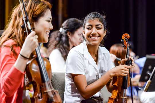 Color image of First Associate Concertmaster Susie Park playing next to a young Cuban violinist in a Side by Side rehearsal. 2015.