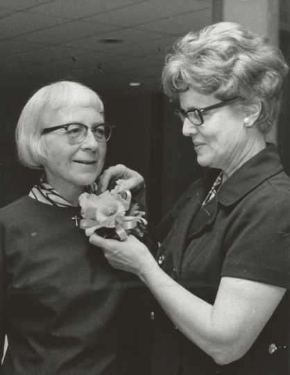 Black and white photograph of St. Catherine's alumna Betty Hubbard (right) pinning a corsage on Alice Gustava Smith (Sister Maris Stella, left) at the College of St. Catherine in 1971. Photographed by P.J. Strasser.