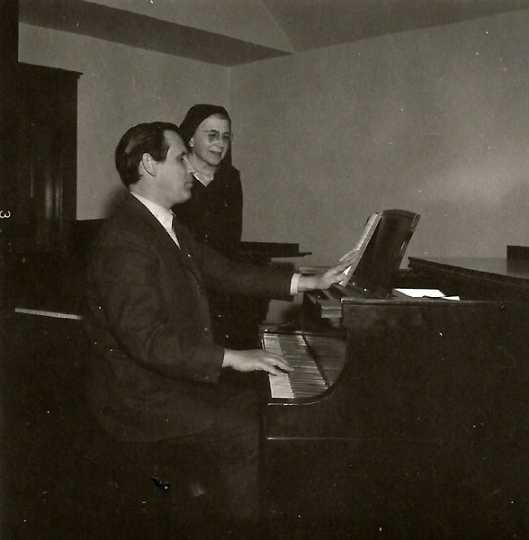Black and white photograph of composer Paul Fetler (at the piano) with Alice Gustava Smith (Sister Maris Stella), c.1969.