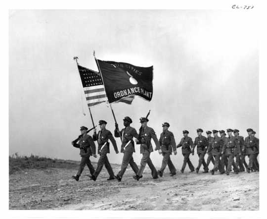 Soldiers marching with Twin Cities Ordnance Plant flag