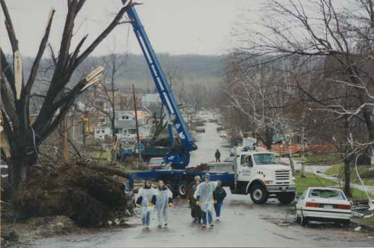 Photograph of volunteers clearing debris from a street in St. Peter.