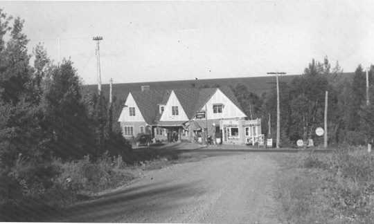 Black and white photograph of Stickney Inn and Store, facing south, from Cramer Road, with gas station at right, ca. 1940.