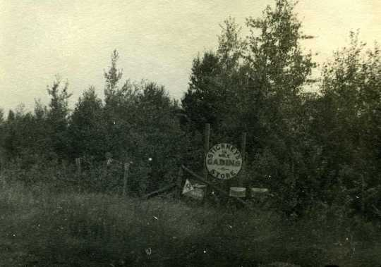 """Black and white photograph of a sign on Highway 61 marking """"Stickney's Cabins & Store,"""" ca. 1940."""