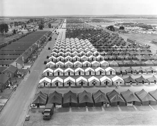 """Black and white photograph of tents and """"hutments"""" at Camp Ripley, 1965."""