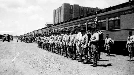 Black and white photograph of guardsmen arriving by train for annual field training at Camp Ripley in 1938.