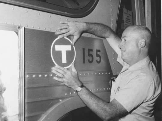 "A transit worker applies a ""T"" (for transit) decal to one of the old Twin City Lines buses before being sent out on the streets under new management for the first time in September 1970. All of the former TCL buses were eventually repainted a solid red before until they were replaced. Photo by the St. Paul Pioneer Press; used with permission."
