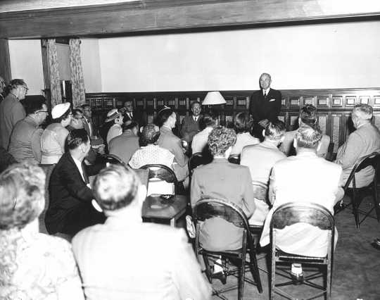 Black and white photograph of former president Harry Truman speaks to guests in Nelson Hall, the post's headquarters, in July 1953