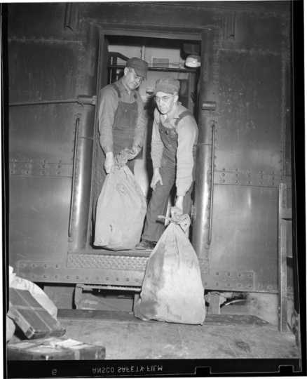 Railway Mail Service clerks load mail bags onto a Great Northern Railway Post Office car at the St. Paul Union Depot.