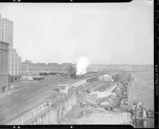 Looking east from the Robert Street bridge at a Milwaukee Road freight train behind double-headed steam locomotives passing the St. Paul Union Depot.