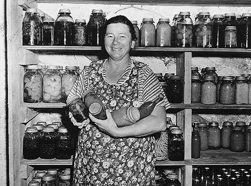 Woman with canned vegetables, part of Farm Security Administration program.