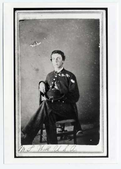 Photograph portrait of Martin Webb. He is seated in a chair with his legs crossed and he is wearing his uniform.