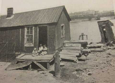 Black and white photograph of a shack and outhouse, river's edge, 1917