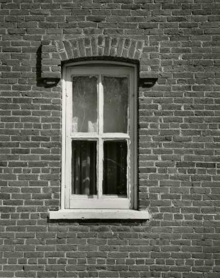 Black and white photograph of a window in the Arnold Nietfield house in Meire Grove.