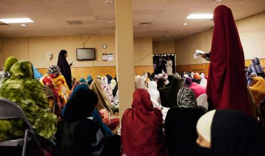 Color image of Somali women pray in the women's prayer room at Dar Al-Hijrah during the holy month of Ramadan, 2013.