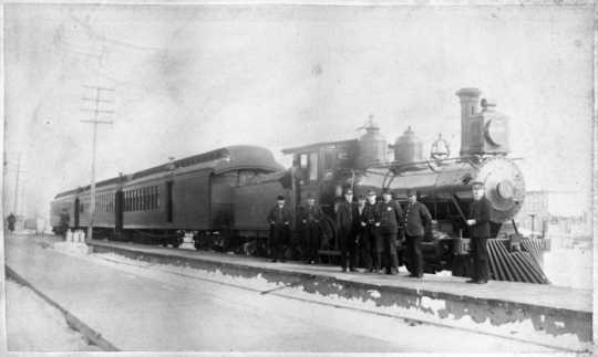 St. Paul and Duluth Railroad Company train and several railroad men, including John Wesley. Blair was an African American porter on the Eastern Minnesota train that rescued hundreds of people from the fire in Hinckley. He was honored as one of the heroes. He is second from the right in the photograph.