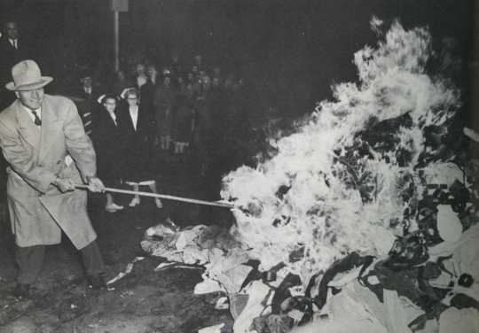 """Governor Luther Youngdahl setting fire to restraints at Anoka County Hospital, October 31, 1949. Photograph by Hi Paul. Published in the St. Paul Pioneer Press on November 1, 1949, with the article, """"Halloween Fire Heralds Reform—Anoka State Hospital Burns Straitjackets."""" Original caption: """"A flaming pile of strait jackets, manacles, and straps marked the end of the use of restraints at the Anoka State Hospital Monday night. Gov. Youngdahl, the moving force behind Minnesota's mental health program, is sho"""