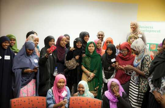 Color image of participants in a leadership development program gather around Malala Yousafzai (at center, in green) at the Confederation of Somali Community in Minnesota in August 2016.