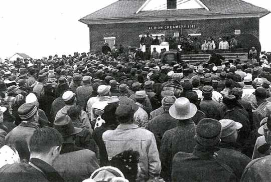 Black and white photograph of a crowd of more than a thousand people gathered on March 7, 1963, in front of the Albion French Lake Creamery.