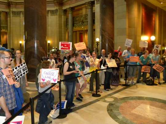 Color image of demonstrators gathered at the State Capitol in St. Paul to show their opposition to Minnesota Amendment 1. Photographed on May 20, 2011, by Flickr user Flickr user Fibonacci Blue.