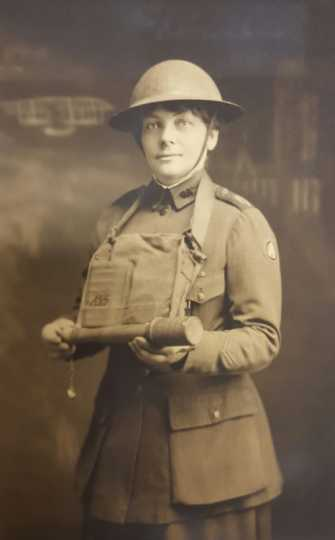 Black and white photograph of YMCA worker Julia Swenson holding a grenade, ca. 1919. Photographer unknown.