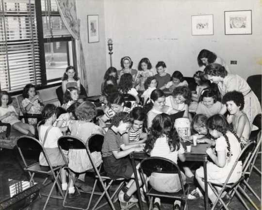 """Black and white publicity photograph (taken c.1930) showing arts and crafts activates for kids enrolled at """"Stay at Home Camp,"""" a summer camp developed by the Jewish Center Activities Association, for the growing number of families joining the J. E. C."""