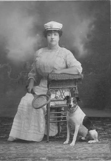 Photograph of Mrs. Emile Amblard sitting on a wicker chair with a tennis racquet in ther hand, a boat cap on her head, and a dog seated by her side. Circa 1910..