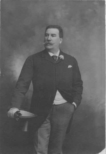 Photograph of Emile Amblard leaning on a table, holding his gloves and wearing a boutonniere. Circa 1910.