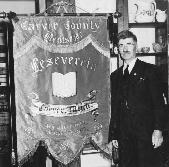 A black and white photograph showing CCHS President O.D. Sell in Mayer with a donated banner from the German Reading Society.