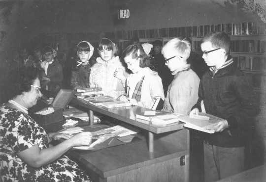 Photograph shows children waiting to check out books at the Waconia Public Library