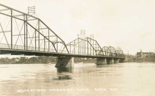 Black and white postcard image of the Anoka–Champlin Mississippi River Bridge, originally built in 1884, ca. 1920.