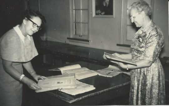 Black and white photograph of Eunice Morberg and Mae Rideout looking at Crookston BPW scrapbooks, 1959.