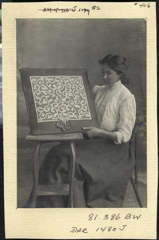 photograph of a young woman displaying bobbin lace