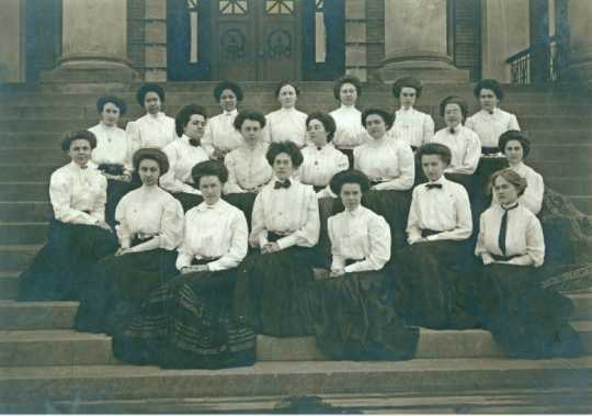 Black and white photograph of St. Catherine's College, class of 1908, on the steps of Derham Hall.