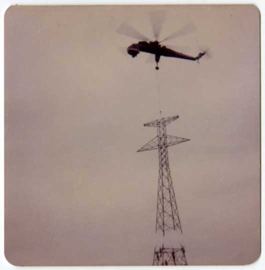 A crane helicopter lining up a power-line tower's top portion with its base during construction of a high-voltage power line through Grant County, Minnesota, 1976-1978.
