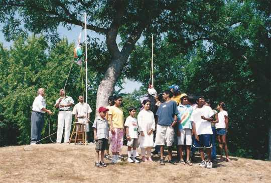 Color image of picnic attendees in St. Paul raise the national flag of India at an event held to celebrate India's independence from Great Britain. Photographed by Anoop Mathur in August 2003.