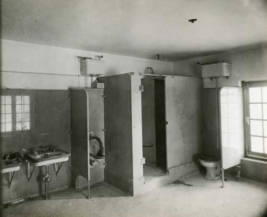 Black and white photograph of a the mail carrier's (men's) toilet inside the Anoka Post Office, January 11, 1917.