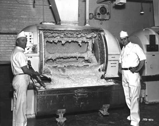 Two men posing next to a Ry-Krisp batter-mixing machine.