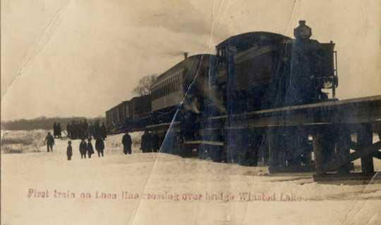 Black and white photograph of the first train on the Luce Line railroad crossing over the bridge at Winsted Lake, ca. 1900.