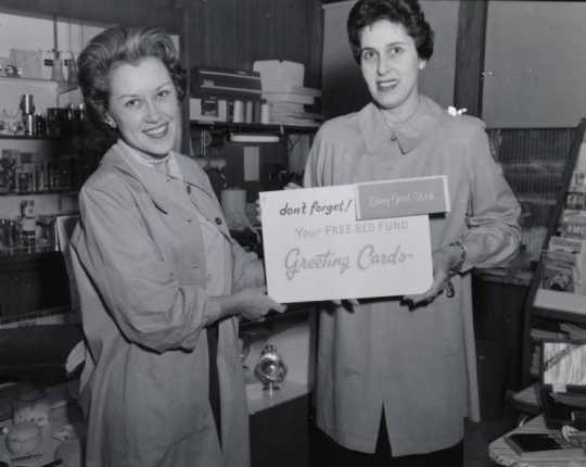 Black and white photograph of two members of the Mount Sinai Women's Auxiliary posing in the Mount Sinai Hospital gift shop holding a sign advertising greeting cards, c.1954.