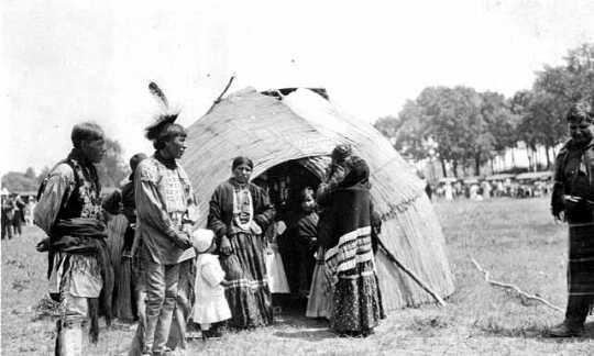 Ojibwe Indians standing by bull rush wigwam