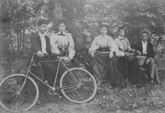 Henrietta Paist and others posed outdoors with a bicycle