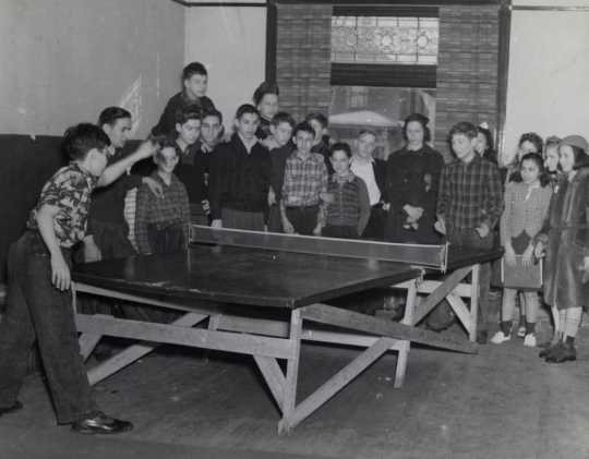 Black and white photograph of two boys playing ping pong at the Jewish Educational Center Annex while a group of children looks on, 1940.