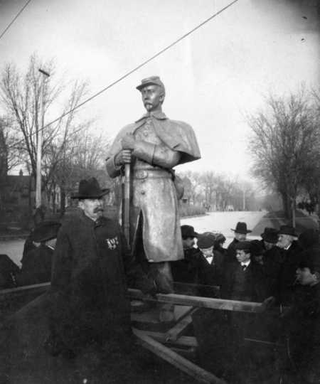 Black and white photograph of Josias King standing in front of a bronze statue patterned after his likeness, 1903.