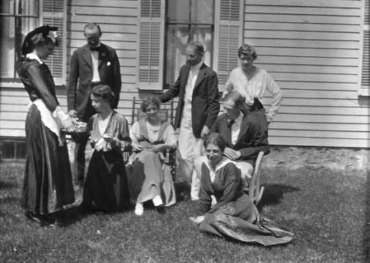 Black and white photograph of Sinclair Lewis and friends, ca. 1916. Lewis sits in the rocking chair at right; his wife, Grace Hegger Lewis, wears a maid's uniform and stands at left.