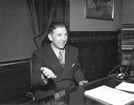 Black and white photograph of Floyd Olson seated at a desk, 1936.