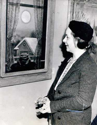 """Black and white photograph of Elsa Laubach Jemne viewing Clement Haupers' oil painting """"Early Moon"""" in St. Paul, 1938."""